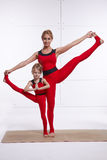 Mother daughter doing yoga exercise, fitness, gym wearing the same comfortable tracksuits, family sports, sports paired. Mother and daughter doing yoga exercise royalty free stock photos