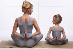 Mother daughter doing yoga exercise, fitness, gym wearing the same comfortable tracksuits, family sports, sports paired. Mother and daughter doing yoga exercise royalty free stock image