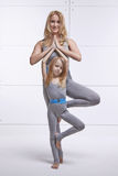 Mother and daughter doing yoga exercise, fitness, gym wearing the same comfortable tracksuits, family sports, sports paired. Holding one leg up royalty free stock photos