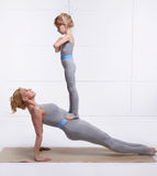 Mother and daughter doing yoga exercise, fitness, gym wearing the same comfortable tracksuits family sports, sports paired woman p Stock Image