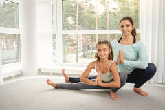 Mother with daughter doing yoga exercise Stock Images