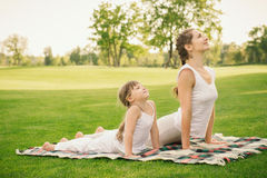 Mother with daughter doing yoga exercise Royalty Free Stock Photography
