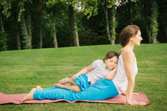 Mother with daughter doing yoga exercise. Young mother and daughter meditating and doing yoga exercise in the city park Royalty Free Stock Images