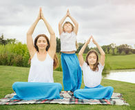 Mother with daughter doing yoga exercise. Young mother and daughter meditating and doing yoga exercise in the city park Royalty Free Stock Photos