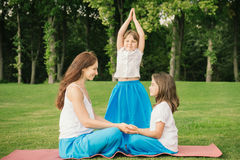 Mother with daughter doing yoga exercise. Young mother and daughter meditating and doing yoga exercise in the city park Stock Photography