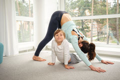 Mother with daughter doing yoga exercise. Young mother and daughter doing morning yoga exercise at home with big windows on background Royalty Free Stock Images