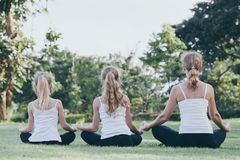 Mother and daughter doing yoga exercises on grass in the park at Royalty Free Stock Photo