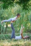Mother and daughter doing yoga exercises on grass in the park at the day time. Young sporty mother and cute little daughter doing yoga exercises on grass in the Stock Images