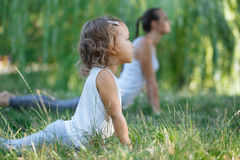 Mother and daughter doing yoga exercises on grass in the park at the day time. Young sporty mother and cute little daughter doing yoga exercises on grass in the Royalty Free Stock Images
