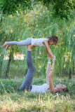 Mother and daughter doing yoga exercises on grass in the park at the day time. Young sporty mother and cute little daughter doing yoga exercises on grass in the Stock Photos