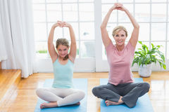 Mother and daughter doing yoga on fitness mat Stock Photos