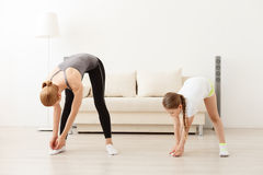 Mother and daughter doing yoga together. I can touch my toes. Young mother and daughter doing doing fitness exercises at home Stock Image