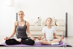Mother and daughter doing yoga together Stock Photos