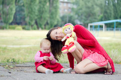 Mother, Daughter and Doll. For a walk in the park royalty free stock image