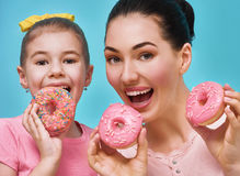 Mother and daughter with donuts stock photos