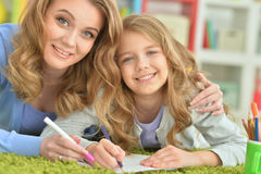 Mother and daughter draw. On a green carpet Royalty Free Stock Photos