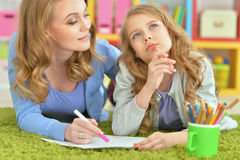 Mother and daughter draw. On a green carpet Stock Images