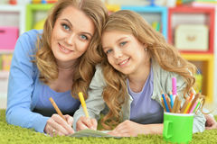 Mother and daughter draw. On a green carpet Royalty Free Stock Images