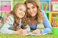 Mother and daughter draw. On a green carpet Stock Photography