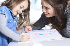 Mother and daughter drawing in a book on the Stock Image