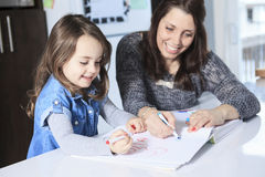 Mother and daughter drawing in a book on the Stock Photo