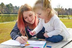 Mother and daughter drawing colors in a park Stock Images