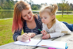 Mother and daughter drawing colors in a park Royalty Free Stock Photo