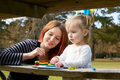 Mother and daughter drawing colors in a park Royalty Free Stock Image
