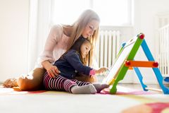 Mother and daughter drawing in the room Royalty Free Stock Photos