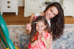 Mother and daughter drawing in the room. Stock Photo