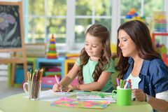 Cute mother and daughter drawing together with felt pens at playroom stock images