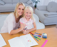 Mother and daughter drawing together and looking at camera Stock Photos