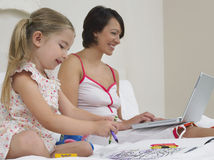 Mother And Daughter Drawing And Using Laptop Royalty Free Stock Images