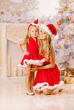 Mother and daughter dressed as Santa celebrate Christmas. Family Stock Image