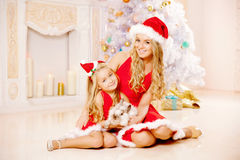 Mother and daughter dressed as Santa celebrate Christmas. Family Royalty Free Stock Photo