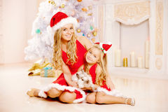 Mother and daughter dressed as Santa celebrate Christmas. Family Stock Photography
