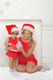 Mother and daughter dressed as Santa with gift, snow Stock Photo