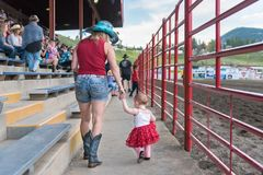 Mother and daughter dressed for Canada Day walked through stands. Williams Lake, British Columbia/Canada - July 1, 2016: a mother and daughter dressed for Canada Royalty Free Stock Images