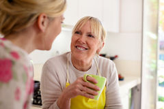 Mother and daughter drinking coffee in kitchen Royalty Free Stock Image