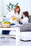 Mother and daughter drinking orange juice Stock Photos