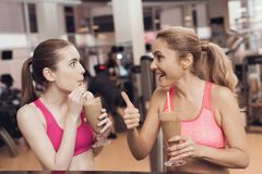 Mother and daughter drinking smoothies at the gym. They look happy, fashionable and fit. royalty free stock photos