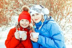 Mother and daughter drinking tea in winter. Happy family mother and child daughter on a winter walk outdoors drinking tea royalty free stock photography
