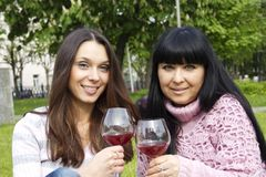Mother and daughter drinking wine outdoors Royalty Free Stock Images