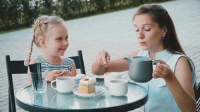Mother with daughter drinks tea in cafe stock video