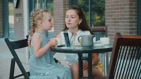 Mother with daughter drinks tea in cafe stock footage