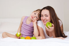 Mother and daughter eat apples Stock Photos
