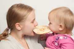 Mother with daughter eat and bitting flatbread Stock Photos