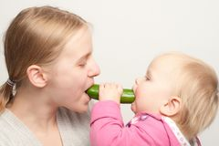 Mother with daughter eat cucumber Stock Photos