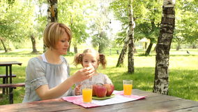 Mother and daughter eat and drink stock video footage