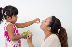 Mother daughter eat fruit Royalty Free Stock Image